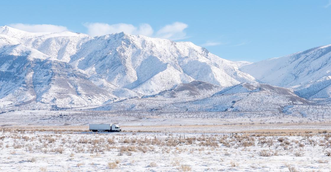 Semi truck driving through snowy mountains
