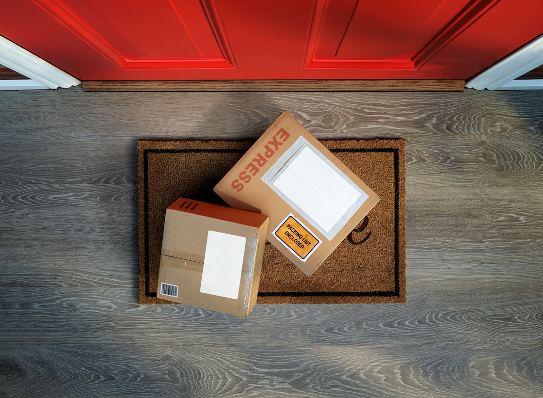 two packages on welcome mat outside of a red door, delivered safely thanks to effective shipping software